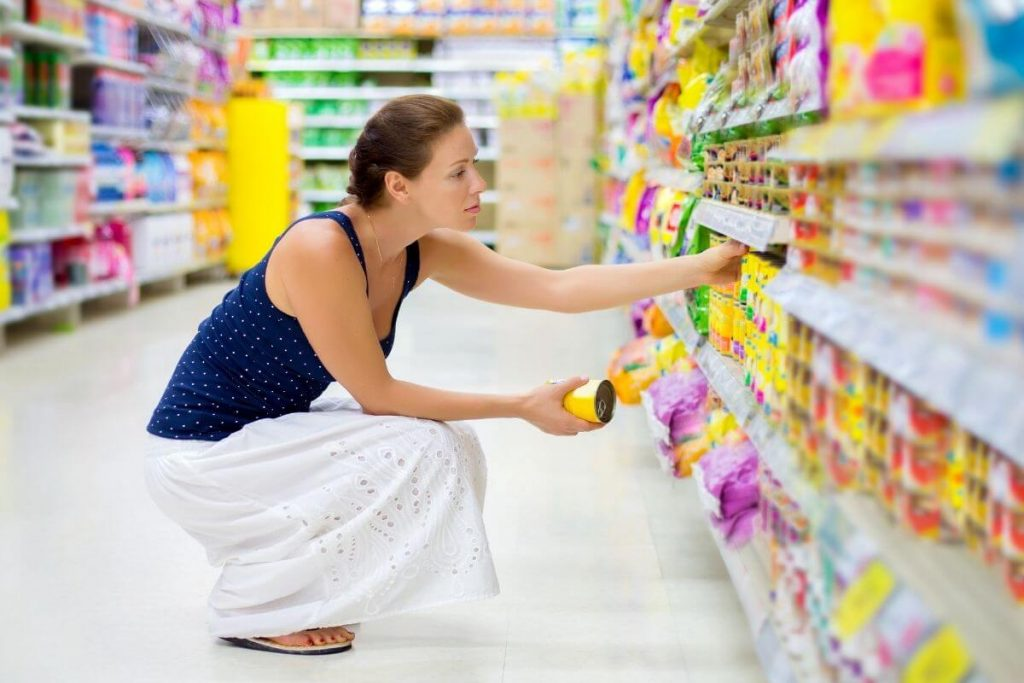 Woman reading labels in a supermarket