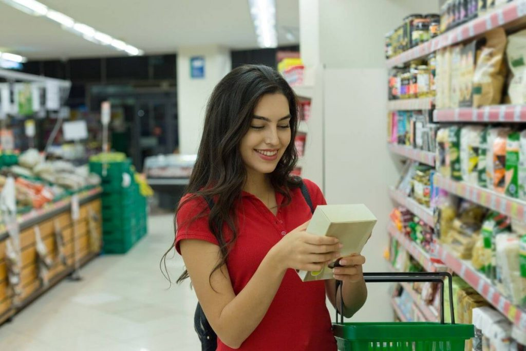 Young woman with long black hair smiling and reading the label on the back of a box