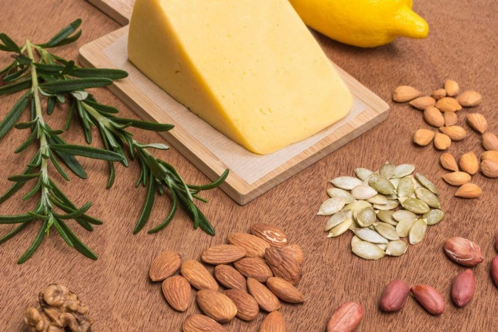 A block of vegan cheese surrounded by a variety of nuts - photo by Oleanaa from Getty Images