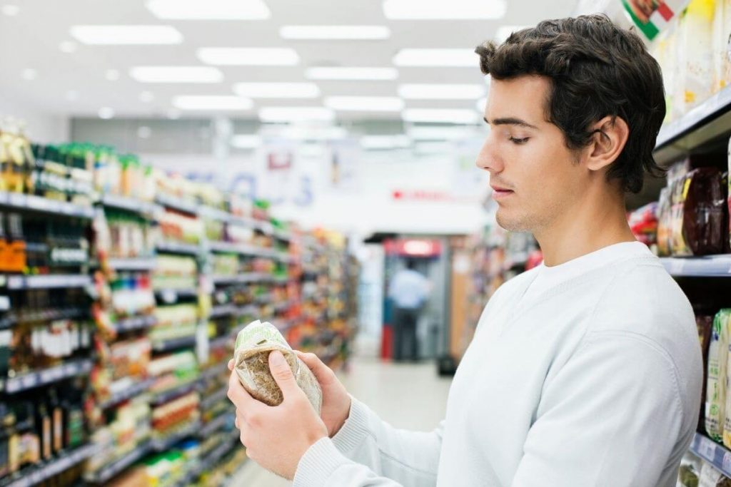 A young man reading the label on a food item in a supermarket