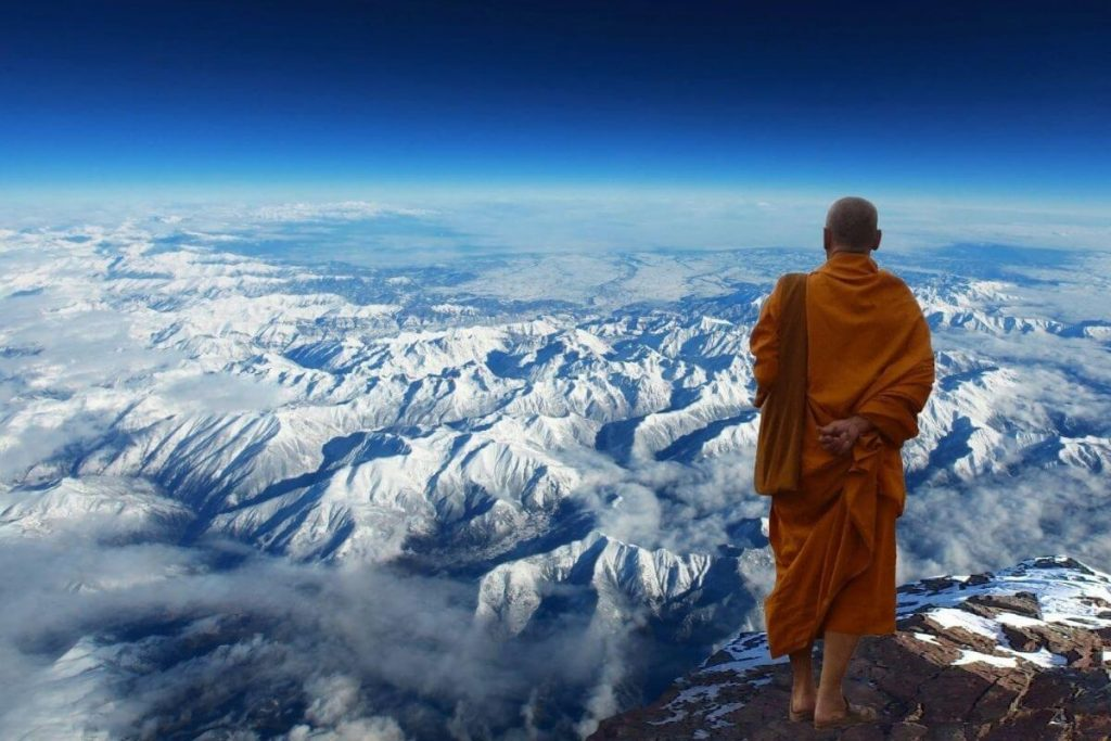 Buddhist monk on the top of a mountain looking at a snow-covered landscape below him