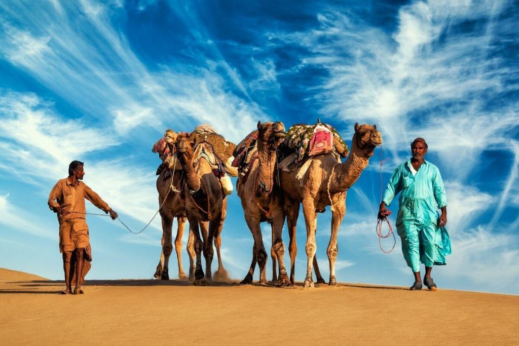 Two camels and two men in the desert with an incredible sky above them